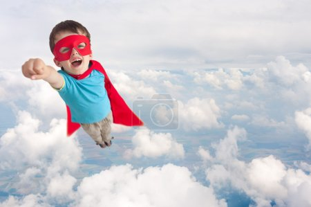 Superhero boy child flying mid air above cloud lev...