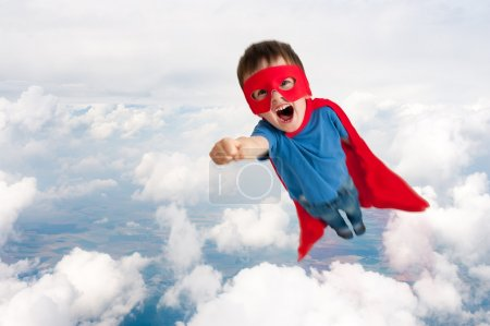 Superhero boy child flying upwards through the clo...