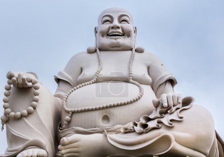 Massive white sitting Buddha statue isolated from decor.
