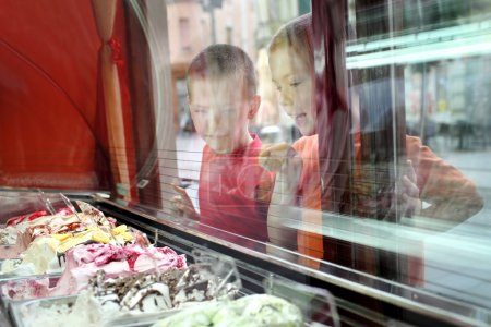 Photo for Two young Caucasian boy looking ice cream in pastry shop, real people with reflection on window - Royalty Free Image