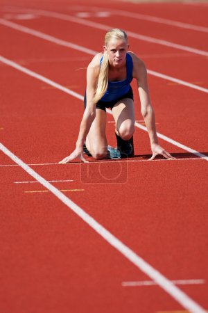 Photo for A young, track and field athlete on the starting block. - Royalty Free Image