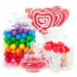A display of various candies in glass containers. ...
