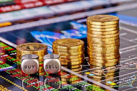 Photo pour Uptrend empile des pièces d'or, dés cubes avec le worsd VENDRE ACHETER sur les graphiques financiers en arrière-plan. Concentration sélective - image libre de droit