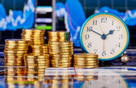 Stacks of golden coins, clock and the financial chart as backgro
