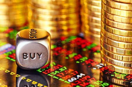 Financial chart, golden coins and dices cube with the word BUY.