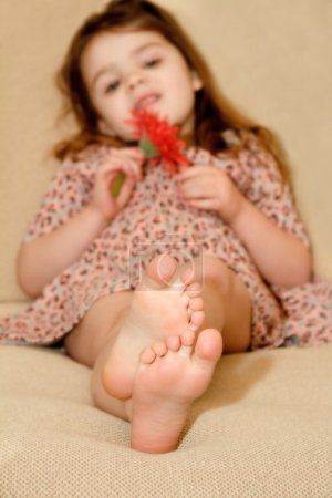 Photo for Focus on feet of little girl resting - Royalty Free Image