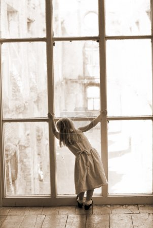 Young girl looking out a window