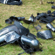 Pieces of medieval armor disposed on grass....