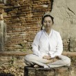 Buddhist woman meditating against ancient temple...