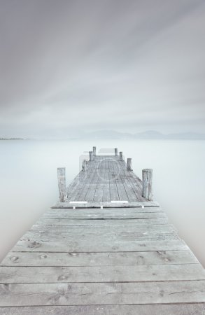 Wooden pier on lake in a cloudy and foggy mood.