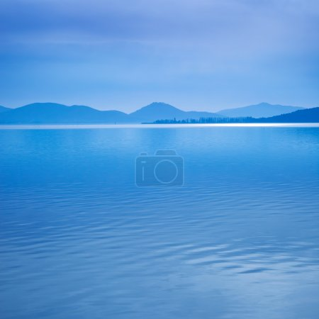 Water surface in a blue morning on the Trasimeno lake, Italy. Hills on background