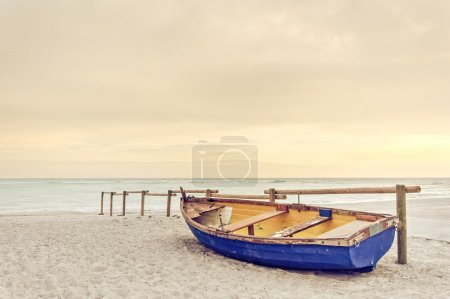 Old yellow blue wooden boat on white beach on warm sunset