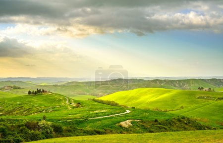 Photo for Tuscany, rural sunset landscape. Countryside farm, cypresses trees, green field, sun light and cloud. Volterra, Italy, Europe. - Royalty Free Image