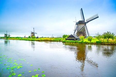 Photo pour Moulins à vent et canal d'eau à Kinderdijk, en Hollande ou aux Pays-Bas. Patrimoine mondial de l'Unesco. Europe. - image libre de droit