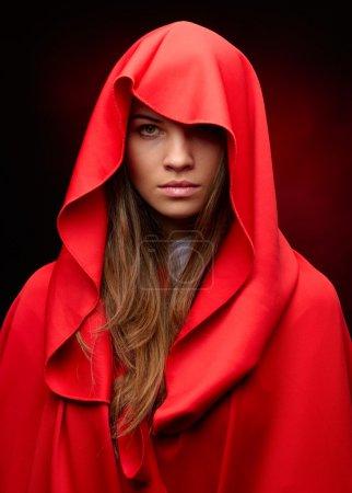 beautiful woman with red cloak in studio