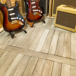 Two electric guitar with amplifiers display around...