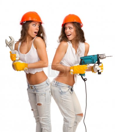 Photo for Gemini girls in orange helmets with an electric drill and a wrench on a white background. - Royalty Free Image