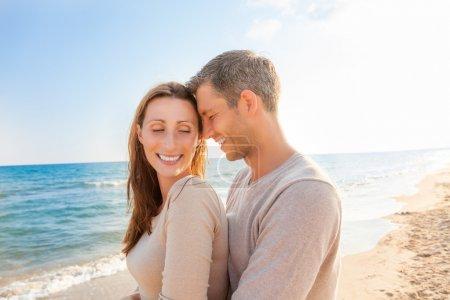Couple enjoying sunbeams at beach...