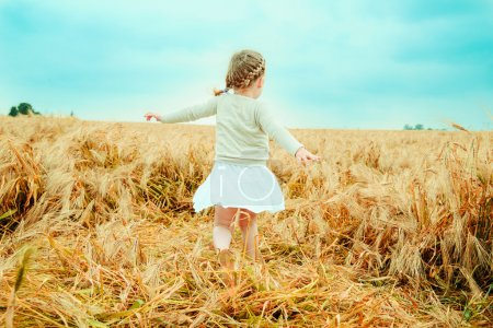 Photo for Dancing child nostalgic in field - Royalty Free Image