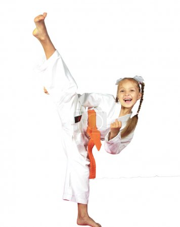 Cheerful girl athlete champion in karate kicking b...