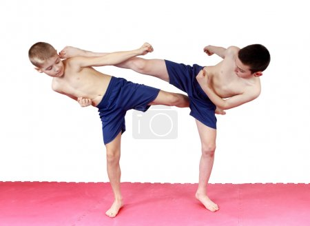 On the mat the boys perform blows legs