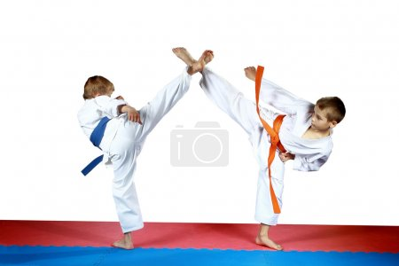 High kicks legs two athletes are training on the red and blue mat