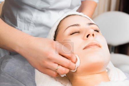 Photo pour Soins de la peau, esthéticienne médicale enlève le masque du visage de la fille - image libre de droit
