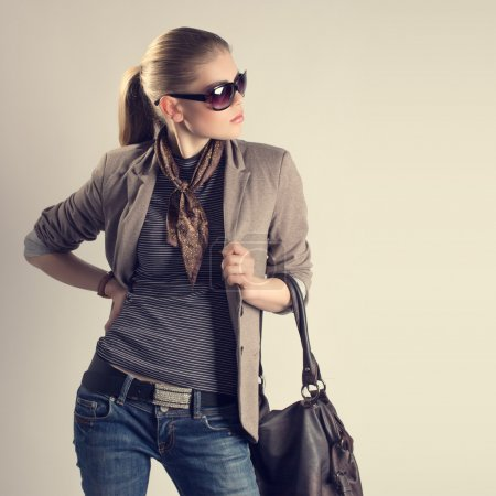 Photo for Shopping woman. Attractive young Caucasian fashion girl in sunglasses holding a leather bag and looking aside. - Royalty Free Image