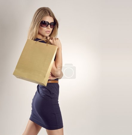 Photo pour Glamour dame blonde dans des lunettes de soleil avec un sac à provisions. Jolie jeune mannequin regardant la caméra en studio . - image libre de droit