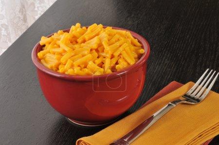 Photo pour Un bol rouge de macaroni et fromage sur un cadre simple - image libre de droit