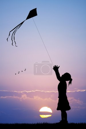 Girl with kite at sunset