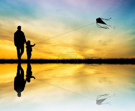 Photo pour Père et fils avec cerf-volant au coucher du soleil - image libre de droit