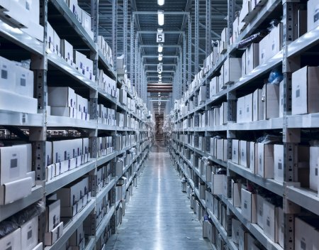 Photo for Interior of the new and modern warehouse space in a well lit large room. Rows of shelves with boxes - Royalty Free Image