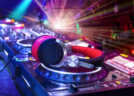 Photo for Dj mixer with headphones at nightclub. In the background laser light show - Royalty Free Image