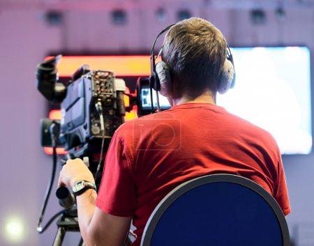 Photo pour Caméraman professionnel avec écouteurs avec caméscope HD à la télévision en direct - image libre de droit