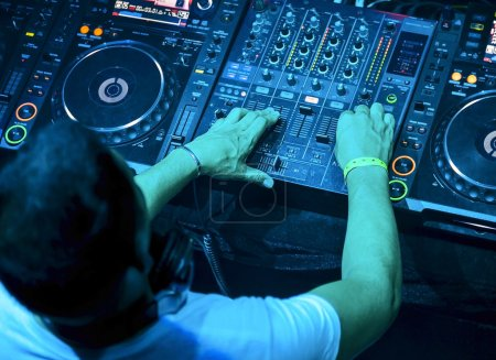 Photo for Dj mixes the track in the nightclub at party. Top view - Royalty Free Image