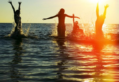 Photo for Silhouettes of young group of people jumping in ocean at sunset - Royalty Free Image