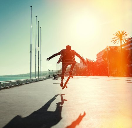 Photo for Silhouette of Skateboarder jumping in city on background of promenade and sea - Royalty Free Image