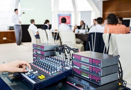 Photo pour Équipement pour les microphones sans fil et homme ajuste le volume sur la console de mixage. enceintes et personnes à la salle de conférence - image libre de droit