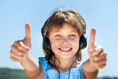 Little girl in headphones listens to music
