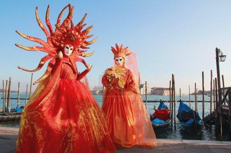 Orange veils masked couple at Venice Carnival