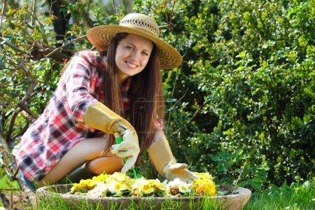 Beautiful happy woman gardening among flowers