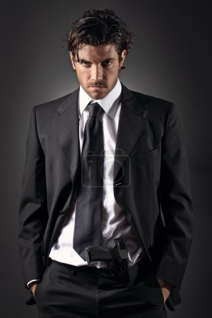 Attractive and elegant man posing with a gun in his trousers