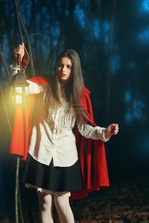 Photo for Little Red riding hood in the dark forest with a lantern . Fantasy and fairy tale - Royalty Free Image