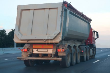 Photo for Big dump truck goes in the evening on highway - Royalty Free Image