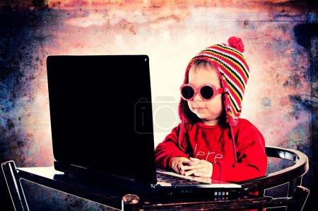Photo pour Mise au point sélective sur l'enfant avec ordinateur portable - image libre de droit