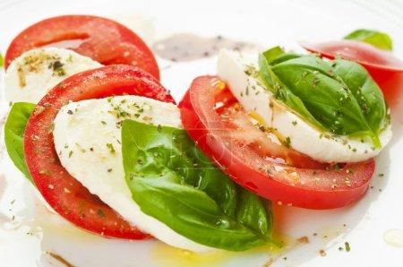 Photo pour Salade Caprese avec mozzarella, tomate et basilic disposées sur la plaque blanche - image libre de droit