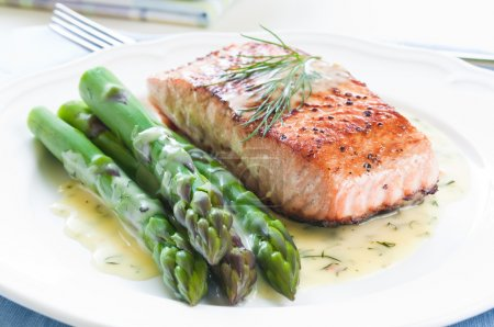 Grilled salmon with asparagus and dill sauce on wh...