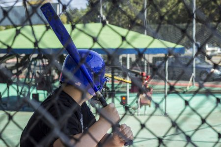 A teen boy at a batting cage