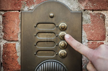 Photo for A visitor pushing a brass, antique doorbell mounted to a brick wall - Royalty Free Image